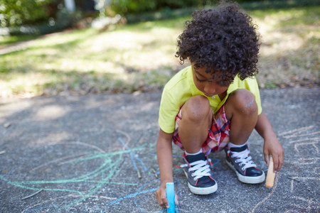 bi: Boy drawing with chalk on sidewalk