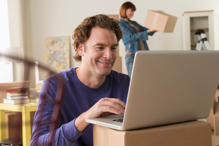 new age: Mature man using computer whilst moving house