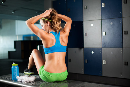 Young woman tying ponytail in gym