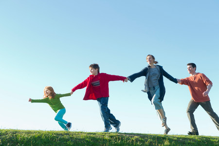 Parents and two children running and holding hands LANG_EVOIMAGES