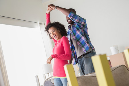 Mid adult couple dancing in new home