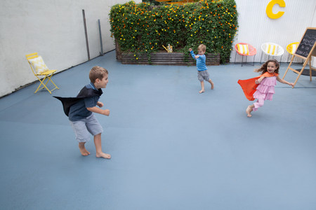 Boys and girl wearing superhero capes playing in back yard LANG_EVOIMAGES