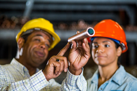 Two warehouse workers inspecting at copper pipe LANG_EVOIMAGES