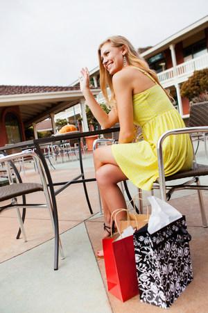 shopper: Woman shopper waving from café LANG_EVOIMAGES