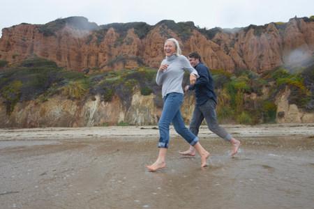 seaboard: Mature couple running on beach