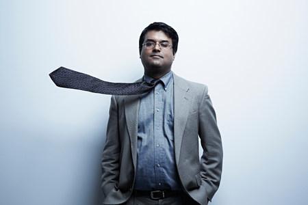 wind blown hair: Studio portrait of businessman with flyaway tie LANG_EVOIMAGES