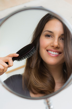 narcissist: Young woman brushing hair in mirror