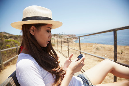 information superhighway: Young woman using cellphone,Palos Verdes,California,USA