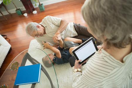 60 65 years: Senior man tickling grandson on rug