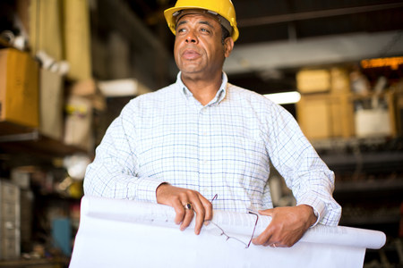 Man in warehouse rolling up blueprint