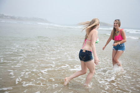 Young women playing in tide on beach