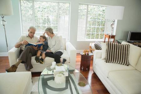 photo album: Grandparents showing boy photo album on sofa