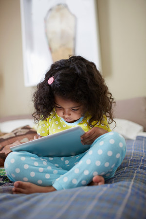 Child sitting on bed using digital tablet