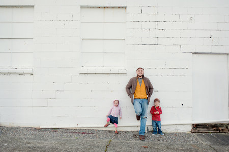 two persons only: Mid adult man and son and daughter leaning against wall,portrait LANG_EVOIMAGES