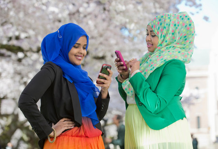 Two young females in park looking at their mobile phones