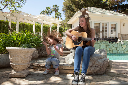 woman hanging toy: Girl with older sister playing guitar LANG_EVOIMAGES