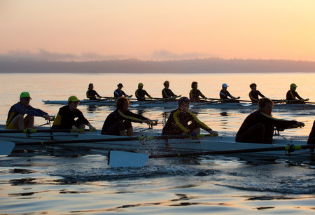 Fourteen people rowing at sunset LANG_EVOIMAGES