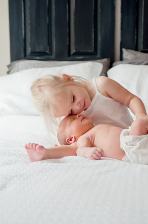 nappy new year: Girl sitting with baby brother on bed