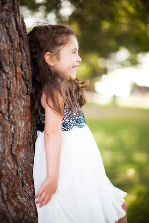 Portrait of girl leaning against tree trunk,smiling