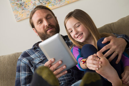 checker: Father and daughter looking at digital tablet