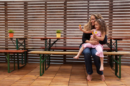 Mother and daughter sitting on bench on patio