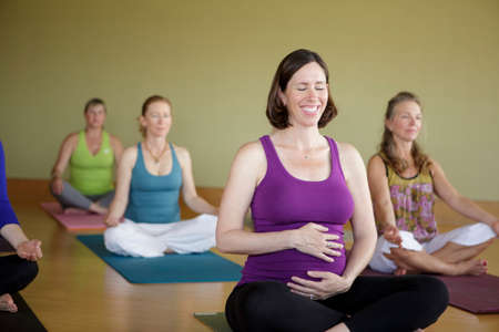 chillout: Pregnant woman in yoga class smiling and holding her stomach