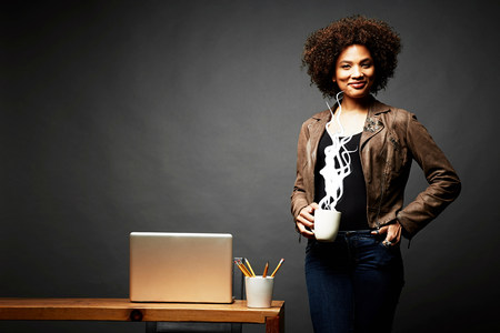 afro caribbean ethnicity: Woman holding cup of steaming hot beverage