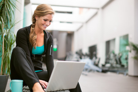 passageways: Young woman in gym corridor using laptop