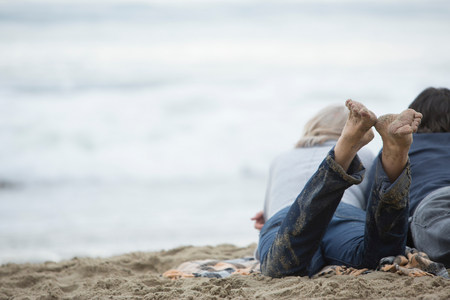 Mature couple lying on beach looking at sea LANG_EVOIMAGES