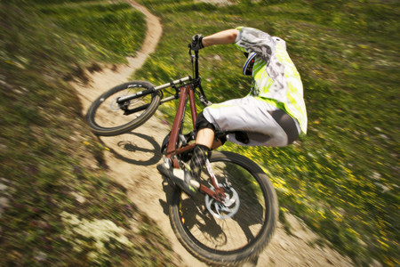 Mountain biker speeding down hill path