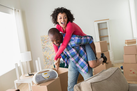 afro caribbean ethnicity: Mid adult couple in new home,man giving woman piggyback