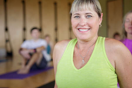 Portrait of mature woman resting with yoga group