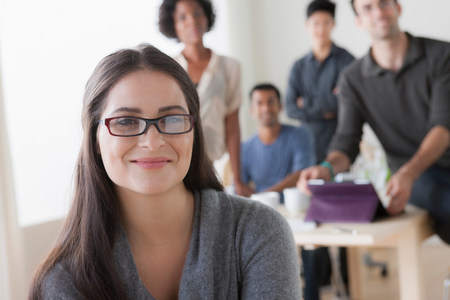 authoritative woman: Portrait of young female office worker in front of colleagues
