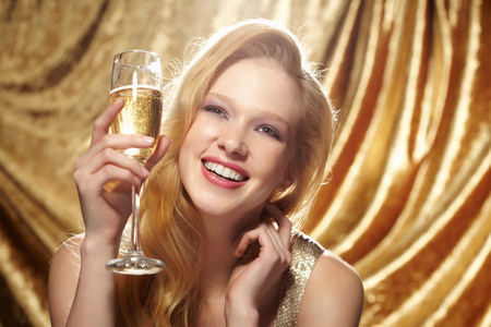 vintage: Candid portrait of young woman holding champagne flute LANG_EVOIMAGES