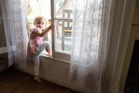 girl in full growth: Child climbing over opened window