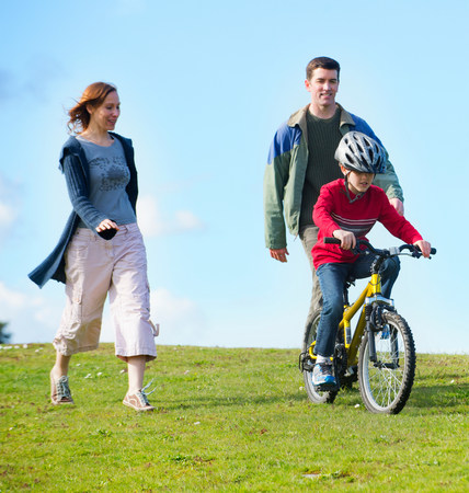 liberating: Parents watching son riding bicycle LANG_EVOIMAGES