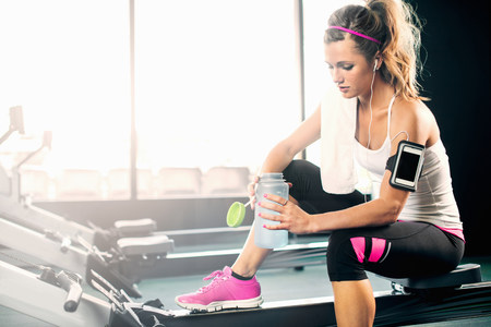 information superhighway: Young woman holding water bottle in gym LANG_EVOIMAGES