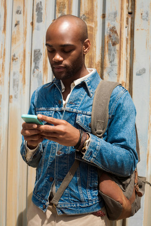fenced in: Portrait of young man using smartphone