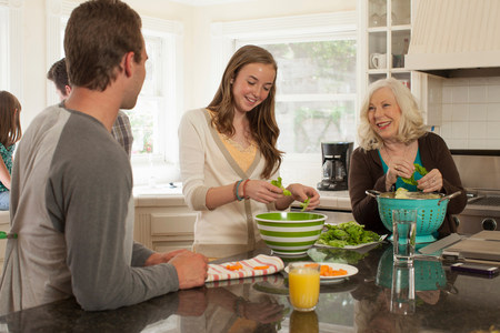 60 65 years: Grandchildren with grandmother preparing food in kitchen