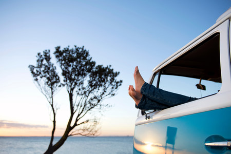 Feet out of camper van window at dusk LANG_EVOIMAGES