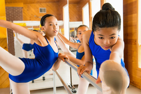 Ballerinas warming up at the barre in ballet school