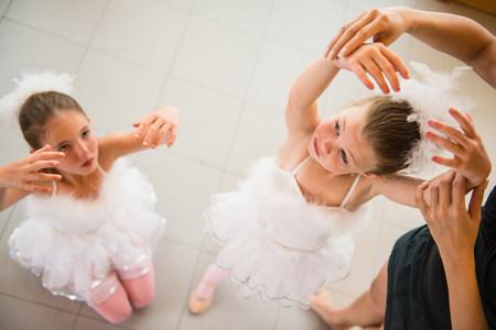 leading education: Mature ballet teacher arranging ballerinas hands