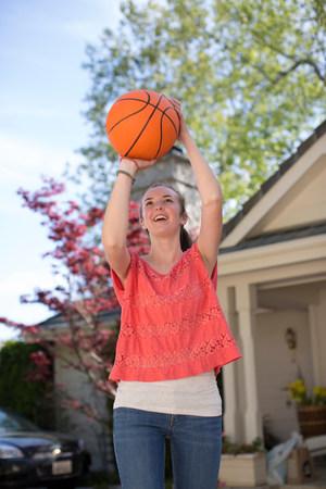 Teenage girl holding basketball above head LANG_EVOIMAGES