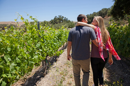 path to romance: Young couple on path in vineyard,woman with arm around man