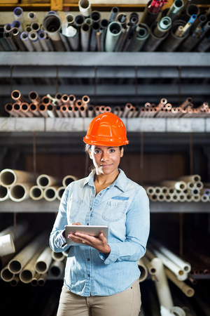 Woman in warehouse with digital tablet
