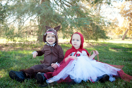 sweet grasses: Toddler twins in woods dressed up as red riding hood and wolf LANG_EVOIMAGES