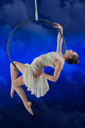 impulsive: Aerialist performing on hoop against blue background
