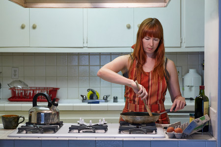 stovetop: Mid adult woman cooking in kitchen