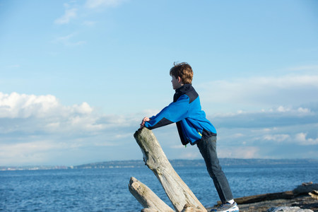 Young boy looking out from Bainbridge Island,Washington State,USA