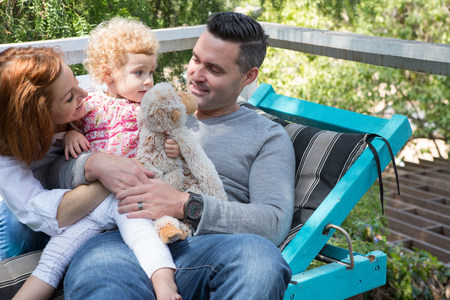 woman hanging toy: Couple on deckchair with child LANG_EVOIMAGES
